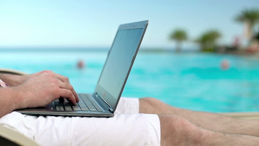 man-with-laptop-on-beach